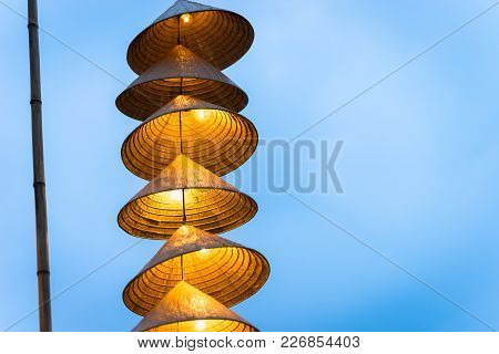 Illuminated Stripe Vietnamese Traditional Conical Hats Hanging On Wire For Decoration, With Blue Sky