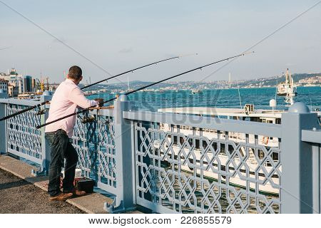 Istanbul, June 15, 2017: A Fisherman From The Local Population Stands On The Galata Bridge And Fishe