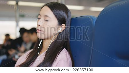 Woman sleeping on ferry and listen to music