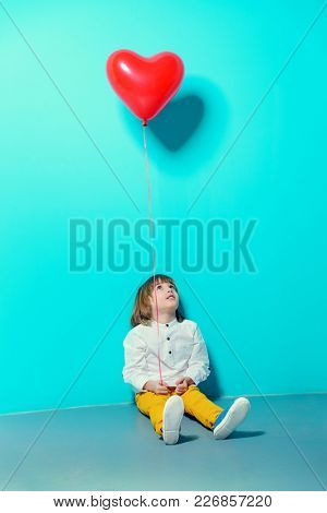 Ð¡ute six-year-old boy holding heart shaped balloon over blue background. Valentine's Day.