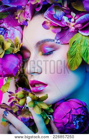 Beauty portrait. Beautiful brunette woman with sensual lilac lips surrounded by flowers. Spring look. Cosmetics, make-up. Perfumery.
