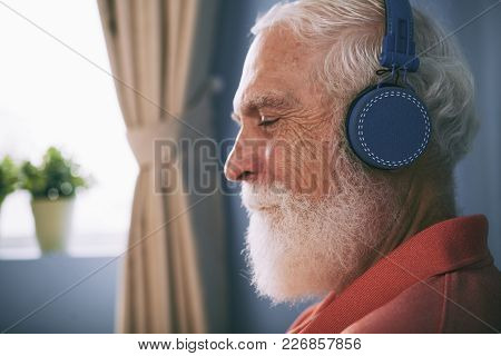 Profile Of Senior Man With White Beard Enjoying Listening To Music Through Wireless Headphones