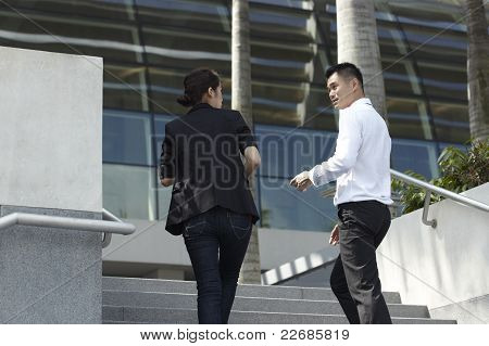 Asian Business Man And Woman Walking Up Steps