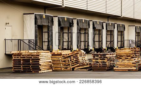 Warehouse Truck Bays With Stacked Wooden Pallets In The Foreground