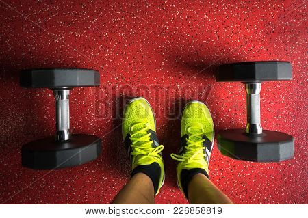 Weights In The Gym With Man Feet Wearing Sport Shoes