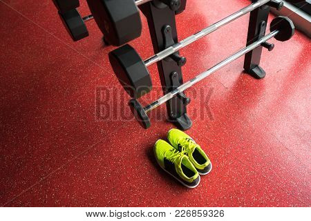 Fitness Rod With Weights And Sport Shoes In Gym