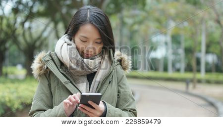 Woman sending text on cellphone at outdoor