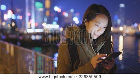 Young Woman using cellphone in Hong Kong at night