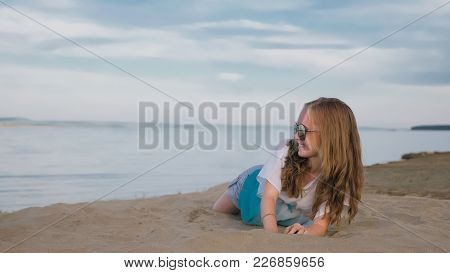 One Beautiful Teenage Girl With Brown Hair Outside On A Beautiful Summer Day. The Woman Is Sitting O