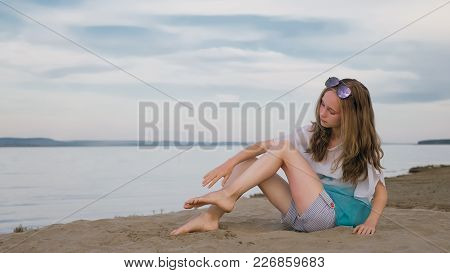 One Beautiful Teenage Girl With Brown Hair Outside On A Beautiful Summer Day. A Girl Is Doing Hersel