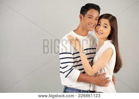 Portrait Of Romantic Asian Couple Embracing On Grey Background, Copy Space To Left