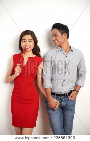 Portrait Of Beautiful Asian Couple Holding Hands While Posing Near Wall On Valentines Day