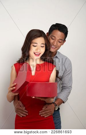 Excited Young Woman Opening Heart-shaped Valentine Gift Box Embraced By Her Boyfriend