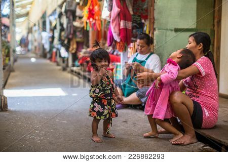 KO CHANG, THAILAND - FEB 15, 2018: Local inhabitants of the Bang Bao fishing village, which consists of houses on stilts built into the sea. Ko Chang consisting of 8 villages with 5,356 inhabitants.