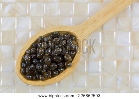 Closeup of fresh papaya seeds in wooden spoon on yellow tile background, top view