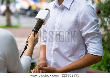 News Journalist With Microphone Interviewing On Street Closeup