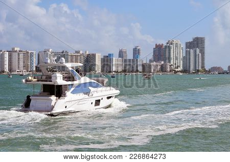 White Luxury Motor Yacht Cruising The Florida Intra-coastal Waterway Off Miami Beach With South Beac