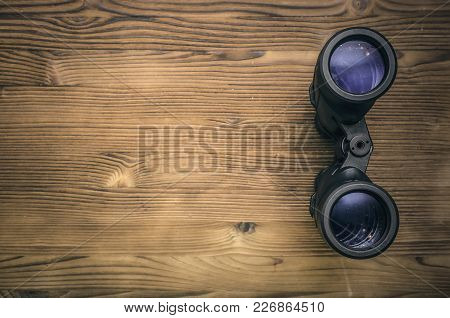 Binoculars On Wooden Table Background With Copy Space For Treasure Map For Example. Find And Search