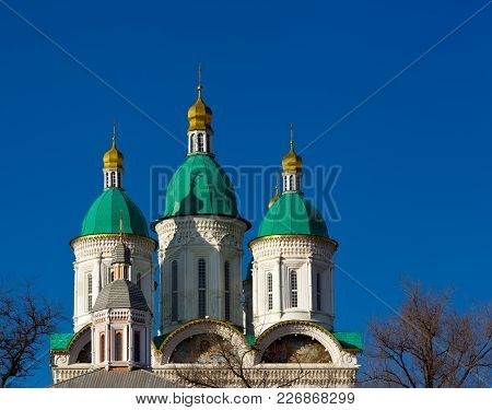 Astrakhan. Cathedral Of The Assumption Of The Blessed Virgin Mary. Golden Domes On A Background Of T