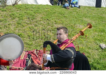 Veliko Tarnovo, April 04 2015, A Man Playing Music With A Bagpipe Lot Of Tourist Are Around Him A Li