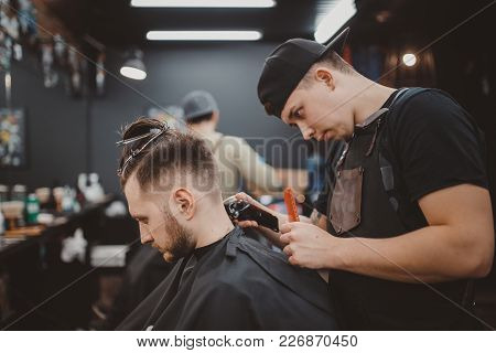 Barber Shop. Master Shaves The Head Of Man Hair Clipper. In Background People