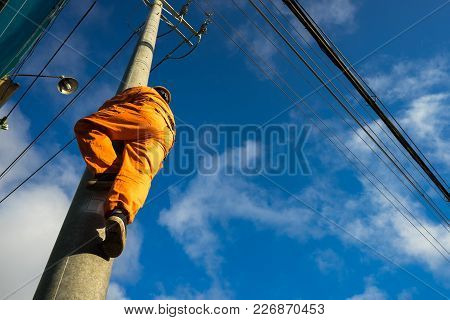 Asian Electrician Climb High On Pole To Repair Electrical System