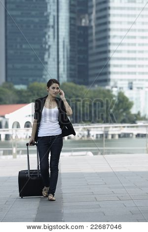Business Woman Walking And Using A Mobile Phone