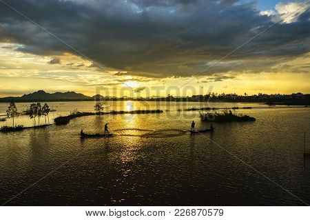 Sunset On Cultivated Field With Fishermen Catching Fish By Throwing Nest In An Giang, South Of Vietn
