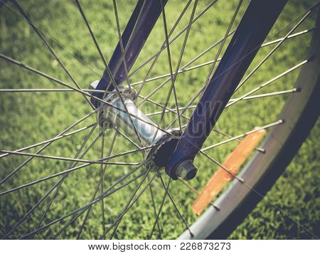Bicycle Wheel In The Summer Green Grass Meadow Field. Close Up Detail