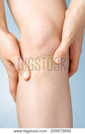 Woman Putting An Adhesive Bandage On Her Leg