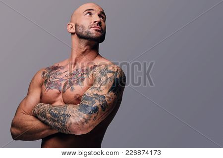 Portrait Of Shaved Head, Muscular Male With Crossed Arms And Tattoos On His Suntanned Body.