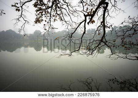 Tree Branches Over Lake Landscape In Winter Season At Hoan Kiem Lake, Center Of Hanoi