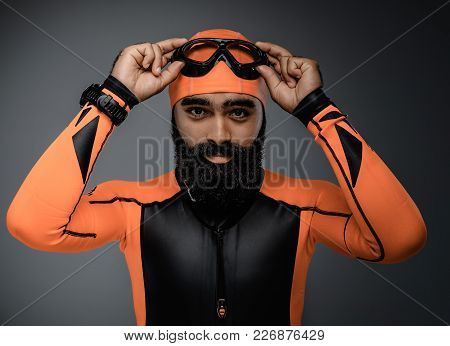 Portrait Of Bearded Male In Scuba Diving Mask And Orange Neopren Diving Suit Isolated On Grey Backgr