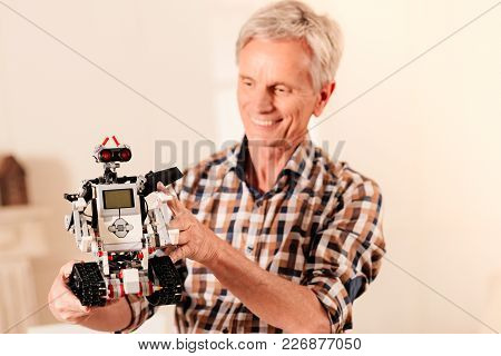 The Work Is Done. Selective Focus On A Self Automated Robot Held By A Satisfied Engineer Grinning Br