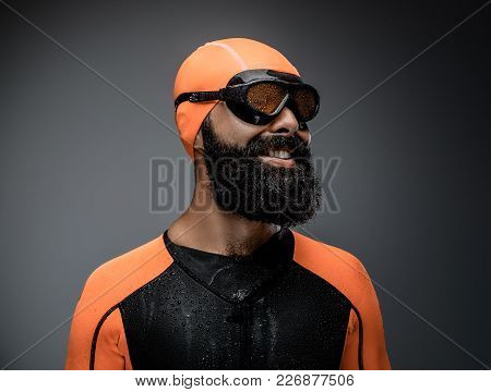 Close Up Portrait Of Bearded Male In Scuba Diving Mask And Orange Neopren Diving Suit Isolated On Gr