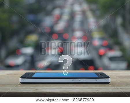 Question Mark Icon On Modern Smart Phone Screen On Wooden Table Over Blur Of Rush Hour With Cars And