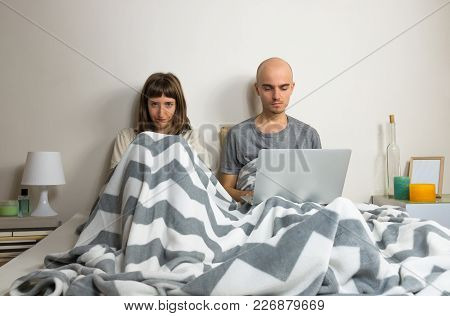 Man Browsing Web In Laptop And Angry Wife Together In Bed. Unhappy, Dissatisfied Young Female Sits W