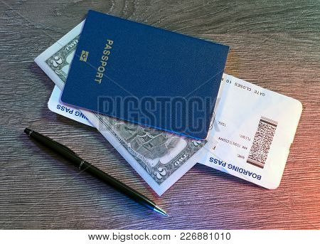 Passports, Boarding Pass, Dollars, Pen Lying On Wooden Table