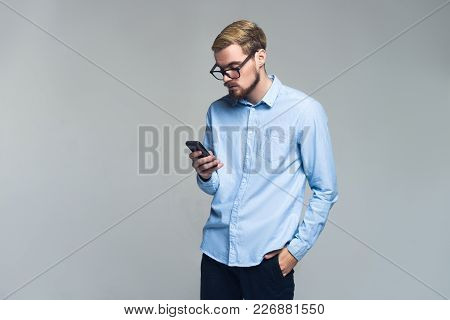 Serious And Handsome. Young Business Man Messaging On His Mobile Phone. Grey Background.