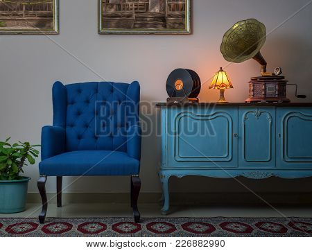 Interior Shot Of Blue Armchair, Vintage Wooden Light Blue Sideboard, Lighted Antique Table Lamp, Old