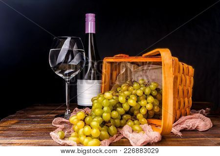 Picture Of Empty Wine Glass, Grapes Of Green On Wooden Basket On Table In Studio