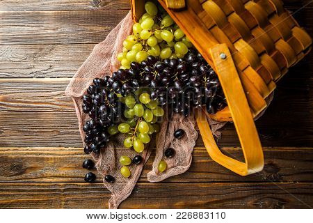 Picture Of Grapes Green And Black In Wooden Basket On Table In Studio