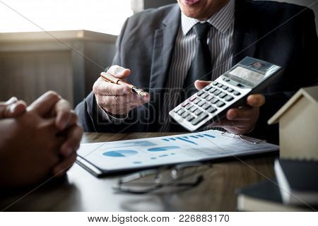 Real estate broker agent being analysis and making the decision a home estate loan to customer, Agent man is using calculator to presentation detail and waiting for his reply to finish. poster