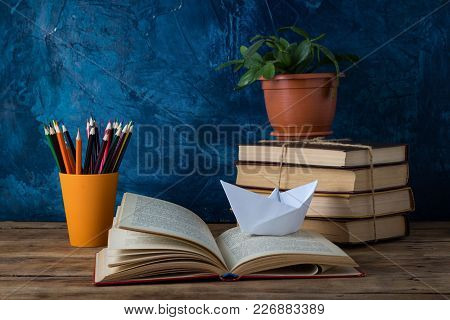Open Book, A Pile Of Books, A Paper Boat, Colored Pencils On A Darkly Blue Background