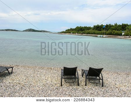 Bench On The Sandy Beach At The Sea On The Background Of Colorful Blue Sky With Clouds At Sunset. Be