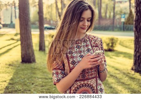 Awesome Young Female With Smartphone In A Summer Wild Park.