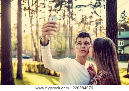 Cute Female Kissing Her Boyfriend When He Taking Selfie In A Park.