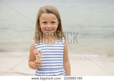 Portrait Of Adorable And Beautiful Blond Young Girl 6 Or 7 Years Old Eating Delicious Ice Cream Smil