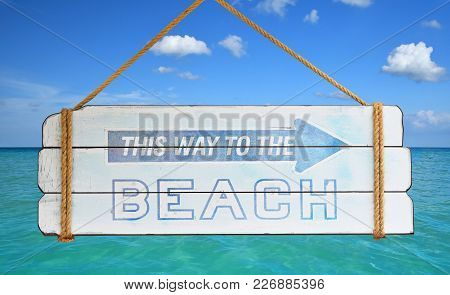 Close Up Old Wooden Directional Arrow Sign With This Way To The Beach Text Hanging Over Background O