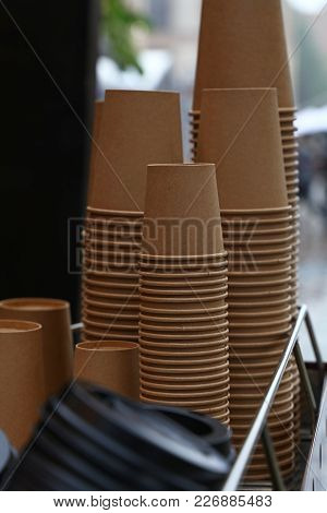 Close Up Stack Of Brown Disposable Kraft Paper Cups On Coffee Machine, Low Angle View